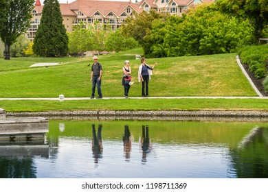 KELOWNA, BRITISH COLUMBIA, CANADA - JUNE 2018: People walking around the edge of a landscaped garden and pond in Kelowna, British Columbia, Canada with reflections in the still waters.