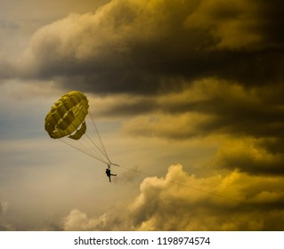 KELOWNA, BRITISH COLUMBIA, CANADA - JUNE 2018: Two people parasaling under a stromy sky in Kelowna, British Columbia, Canada under a dark cloudy sky.