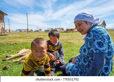 KEL-SUU, KYRGYZSTAN - AUGUST 13: Woman sitting in a grass with her two kids and a dog in a remote Kyrgyz village. August 2016