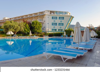 Kemer, Antalya Province / Turkey - July 18 2018: Swimming pool and sunbeds with umbrellas near the hotel at sunny summer morning. Beautiful summer vacation at holiday resort.