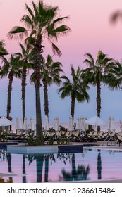 Kemer, Antalya, Turkey - 10/28/2018; Sherwood Exclusive Kemer. Beautiful pink sunset, silhouettes of palm trees, view of the pools and the sea