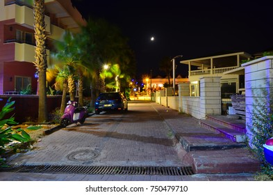 KEMER, ANTALYA, TURKEY - SEPTEMBER 26, 2017: One of many small town streets made with paving stone with some palm trees, parked car and a scooter. Long exposure night photo.