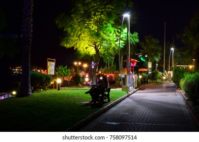 KEMER, ANTALYA, TURKEY - SEPTEMBER 26, 2017: Avenue along the shore at night with a bunch of resting tourists sitting on a bench. Long exposure photo.
