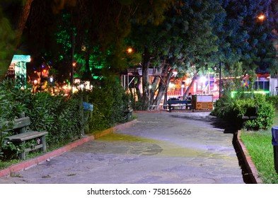 KEMER, ANTALYA, TURKEY - SEPTEMBER 26, 2017: A well lighted walkway with some benches in Kugulu Park near Grand Haber Hotel and Mediterranean Sea shore. Long exposure night photo.