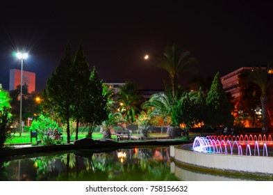 KEMER, ANTALYA, TURKEY - SEPTEMBER 26, 2017: A small pond with a fountain in Kugulu Park with Grand Haber Hotel buildings behind the palm trees. Long exposure night photo.
