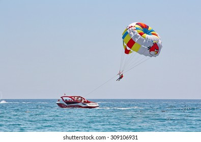 KEMER, TURKEY - AUGUST 14, 2015: Parasailing in a blue sky near sea beach. Parasailing is a popular recreational activity among tourists in Turkey.