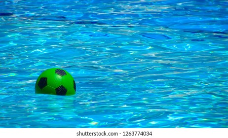 KEMER, TURKEY - JUNE 24 2013: A green ball for football floating in a pool