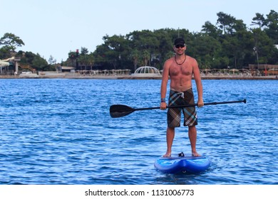 Kemer, Turkey - June 3, 2018 : Attractive young man stand up paddle surfing