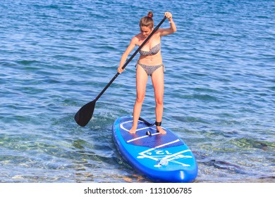 Kemer, Turkey - June 3, 2018 : Attractive young girl stand up paddle surfing