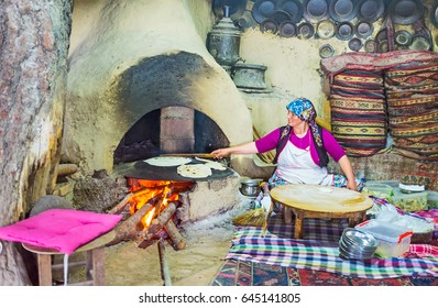 KEMER, TURKEY - MAY 5, 2017: Interior of traditional village kitchen with griddle, heated by wood, standing in clay oven, cook prepares gozleme - Turkish flatbread with toppings, on May 5 in Kemer.