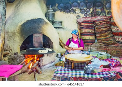 KEMER, TURKEY - MAY 5, 2017: The cook prepares gozleme - traditional flatbread with toppings in the old-styled kitchen with large clay oven and vintage tableware, on May 5 in Kemer.