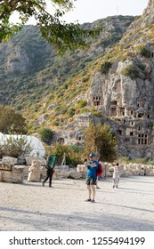 KEMER, TURKEY - OCT, 2018: Ancient lycian necropolis with tombs carved in rocks. Tourists walking near Lycian tombs in Mira.