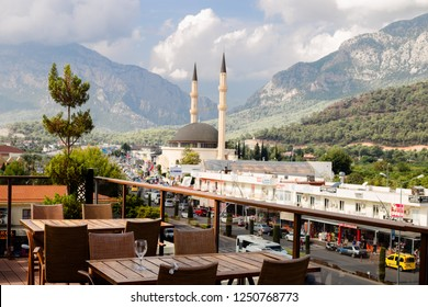 KEMER, TURKEY - OCT, 2018: Cafe on top of tower in Kemer, Turkey. Panoramic view on mountains, mosque, city street. Empty tables in cafe, end of season.