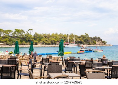 KEMER, TURKEY - OCT, 2018: Empty tables of beach outdoor cafe, Mediterranean sea, Kemer, Turkey. Yachts and green trees on background.