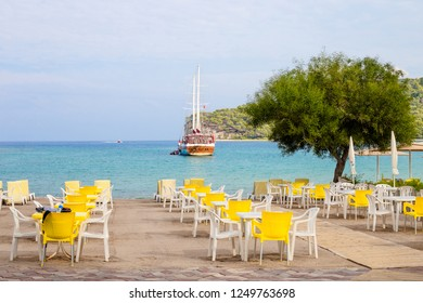 KEMER, TURKEY - OCT, 2018: Empty tables of beach outdoor cafe, Mediterranean sea, Kemer, Turkey. Yellow chairs, green tree, yacht in clean blue water.