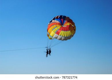 KEMER, TURKEY - OCTOBER 2017: Two people parasailing with colorful parachute against blue sky