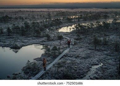 Kemeri, Latvia - October 22, 2017: people taking pictures on wooden path in Kemeri national park swamp on early winter morning with frozen trees and grass.