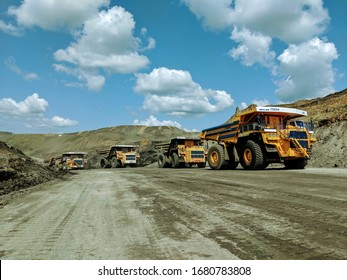 Kemerovo, Russia - August 2019. Heavy Dumb Trucks At The Coal Mining Area. Large Dump Truck Queue in a Quarry.