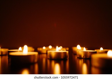 Kemerovo, Russia, burning candles. Candle in female hands on black background. Many candles burning at night. Many candle flames glowing on dark background. Close-up. Free space.