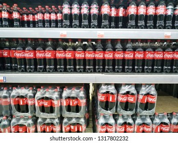 KEMEROVO, RUSSIA, FEBRUARY 18, 2019. Shelves with rows of bottles of Coca Cola in a hypermarket Lenta