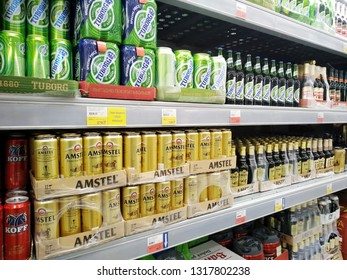 KEMEROVO, RUSSIA, FEBRUARY 18, 2019. Shelves with rows of bottles and cans of beer such as Amstel and Tuborg in a hypermarket Lenta