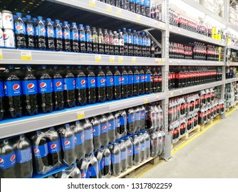 KEMEROVO, RUSSIA, FEBRUARY 18, 2019. A lot of bottles of Pepsi Cola and Coca Cola stand on the shelves in a hypermarket Lenta