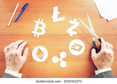 KEMEROVO RUSSIA  FEBRUARY 25 2018. Crypto-currencies. Man cuts out paper cryptocurrency symbols