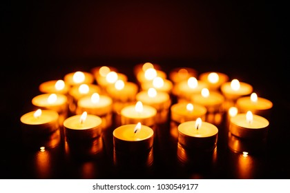 Kemerovo, Russia, fire in the mall, burning candles. Shallow depth of field. Many candles burning at night. Candles background. Many candle flames glowing on dark background. Close-up. Free space.