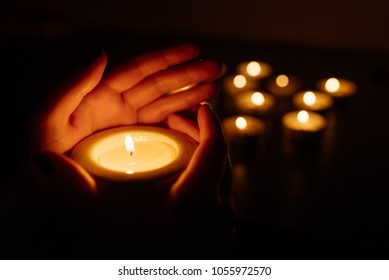 Kemerovo, Russia, fire in the mall, burning candles. Candle in female hands on black background. Many candles burning at night. Many candle flames glowing on dark background. Close-up. Free space.