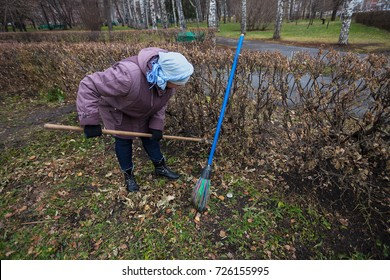KEMEROVO, RUSSIA - NOVEMBER,  1 2016: One woman cleans a rake and broom on the territory of the fallen leaves