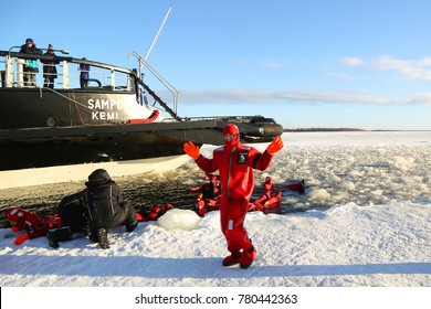 KEMI, FINLAND - FEBRUARY 18, 2017: Unidentified tourists geared up with a survival suit ice swim in frozen Baltic Sea