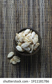 Kenari nut or Canarium nut or Java almond on wooden bowl isolated on wooden mat
