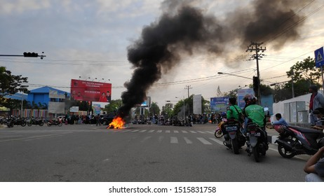 Kendari, 27 september 2019 - tire being burned in the midle of the road at crowd protest or demonstration in Kendari