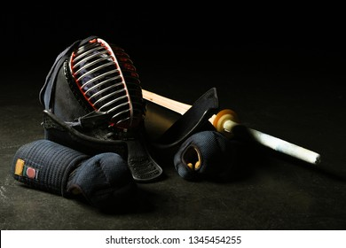 Kendo gloves, helmet and bamboo sword on dark surface