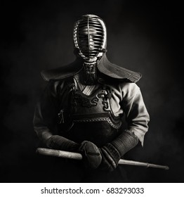 Kendo master standing in traditional armor .He holds bamboo sword shinai.