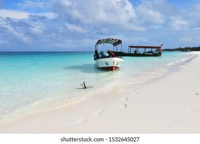 Kendwa, Tanzania - October 3, 2019: Motor boats with locals men moored on the Kendwa beach, Zanzibar, Africa