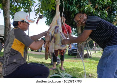 Keningau,Sabah-Sept 1,2017:Muslim butchers trimming a buffalo cow meat to be distributed to muslims in needs during Eid Al-Adha.It is one of the holiest days in the Islamic calendar.