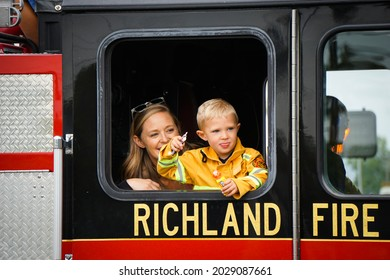 KENNEWICK, WA - AUGUST 21, 2021: Young boy and woman ride in fire truck at the Benton Franklin County Fair parade