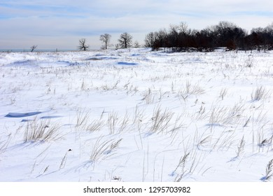 The Kenosha Sand Dunes along the shore of Lake Michigan on a cold day with snow covering the dunes, and some dried grasses exposed above the snow and ice.