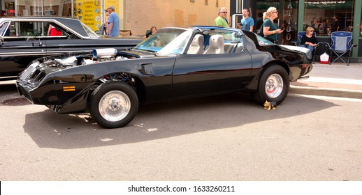Kenosha, Wisconsin / USA - August 31, 2019: A black modified Pontiac Trans Am Firebird with open T-Tops and gray interior on display at the annual local car show.