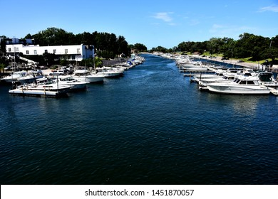 Kenosha, Wisconsin / USA - July 15, 2019:  Looking north at the Kenosha Harbor with rows of vessels on each side of the open water make a clear path back to the boat launch.