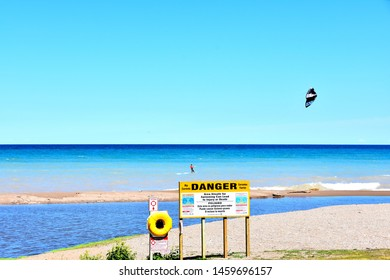 Kenosha, Wisconsin / USA - July 22, 2019:  A lone kite surfer tempting an undertow area in the great lakes of the shore where a river enters into Lake Michigan on a clear windy day.