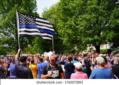 Kenosha, Wisconsin / USA - June 27th, 2020: Thin blue line blue lives matter american flag waves in the wind at back the badge blue lives matter rally to show support to law enforcement in Wisconsin.