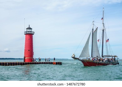 KENOSHA, WI/USA - AUGUST 25, 2019: Adult tourists returning from an afternoon cruise aboard tall ship Red Witch sail past onlookers near Kenosha Lighthouse Studio, a workplace and gallery for artists.