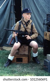 Kent England July 2003. A young reenactor of WW2 wears the uniform of a member of the Hitler Youth and holds a machine gun in a camp setting.