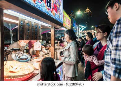 Kenting, Taiwan - February 24, 2018: Vendor prepares food at the Kenting main street night market located in Pingtung County.