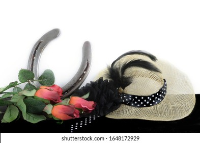 Kentucky Derby photo of a fascinator hot with red roses and a horseshoe. on a black table with white background