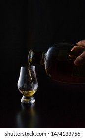 Kentucky straight bourbon whiskey being poured into a glencairn whicky glass in front of a black background. The glass reflections shine off the black wood surface. Portrait orientation with copy.