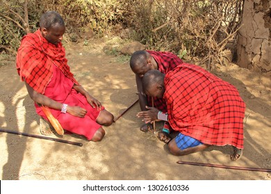 KENYA, AMBOSELI NATIONAL PARK - AUGUST 04, 2018: Three Maasai men show the traditional method to make a fire
