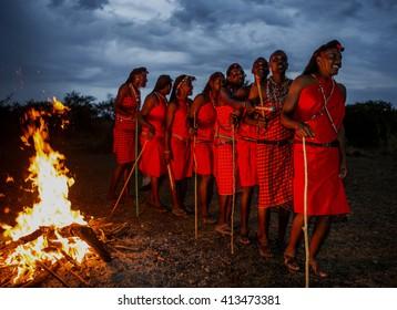 KENYA, MASAI MARA - SEPTEMBER 22, 2015: Warriors the Masai tribe dancing ritual dance around the fire late in the evening. Kenya, Masai Mara, September 22, 2015